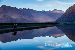 Mountains and motorbike reflecting in the water, Nubra Valley, Ladakh, India