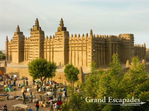 The biggest mud building in the world: the Mosque of Djenne at dawn on a market day, Mali